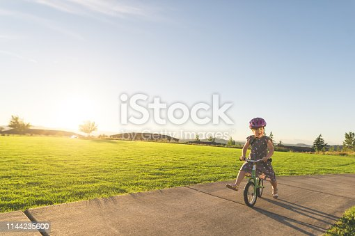 A cute young girl rides her bike along a path through a park on a beautiful summer evening. She is riding toward the camera with a big smile as the sun sets in the background.