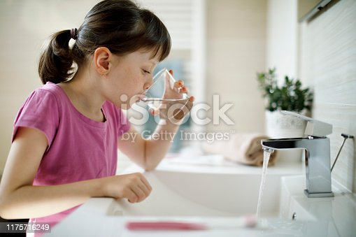 Young girl rinsing mouth in the bathroom