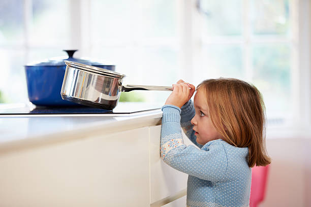 young girl risking accident with pan in kitchen - burning stock pictures, royalty-free photos & images