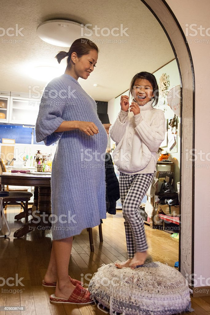 Young girl run to her pregnant mother stock photo