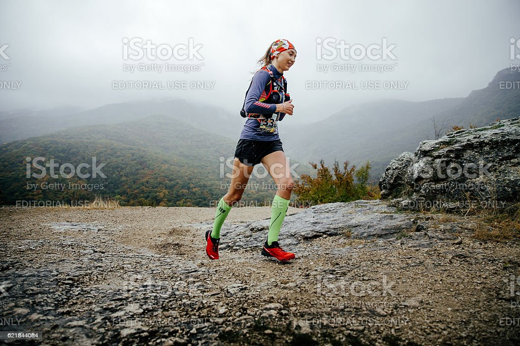 young girl runner running in rain in compression socks stock photo
