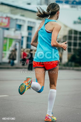 Omsk, Russia -  September 20, 2015: young girl running a marathon, knees in blue kinesiology taping during Siberian international marathon