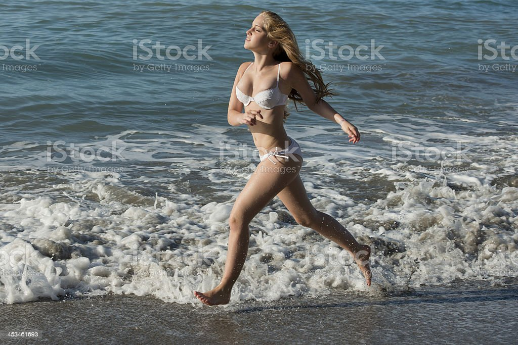 Young girl running at the beach stock photo