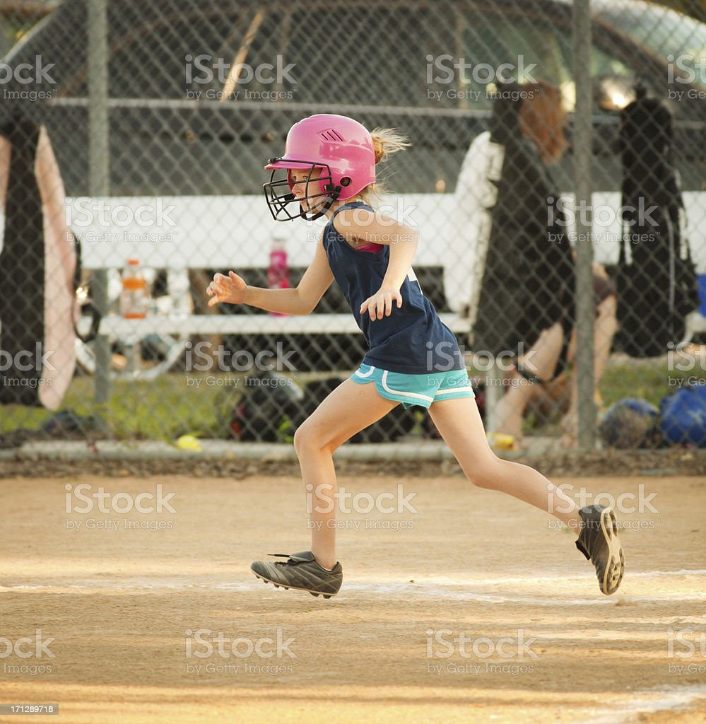 Young Girl Running Bases in Softball Game royalty-free stock photo