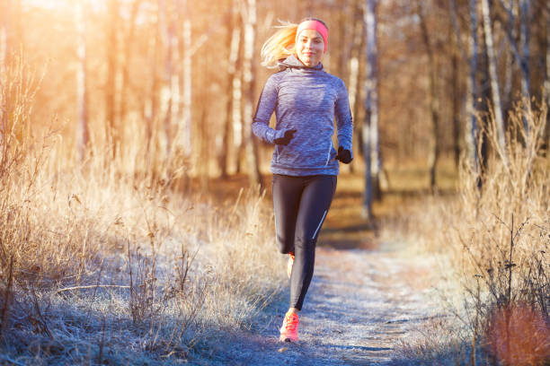 junge mädchen laufen im park im frühwinter - joggerin stock-fotos und bilder