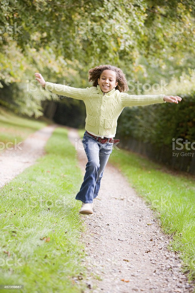 Young girl running on a path outdoors smiling royalty-free stock photo