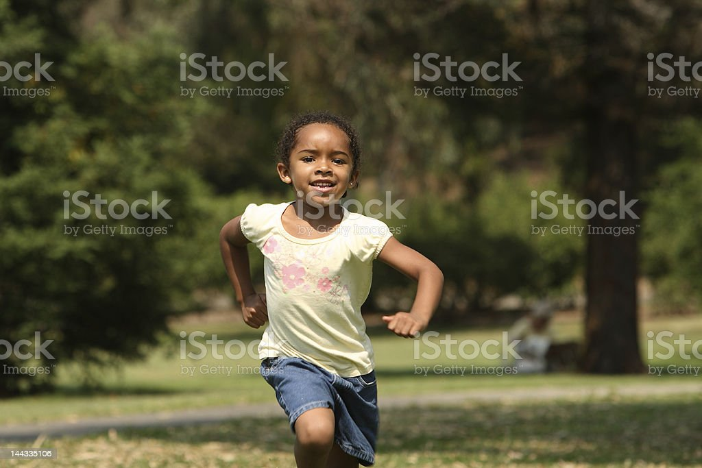 Young girl running outside in a park royalty-free stock photo