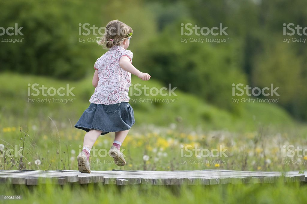 young girl running over a wooden bridge stock photo