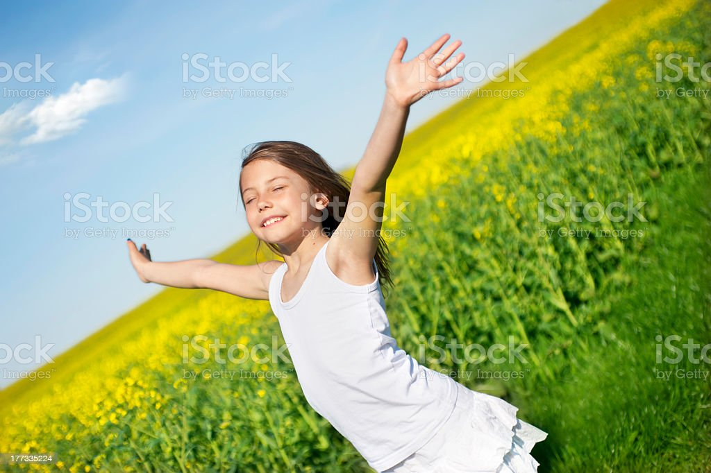 A young girl running through a field with her arms open stock photo