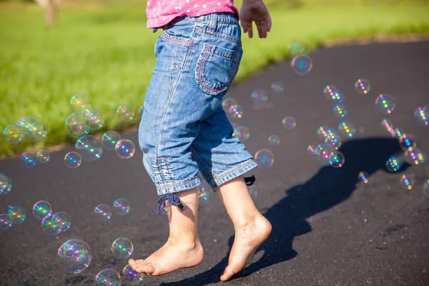 junges mädchen laufen durch blasen - denim caprihosen stock-fotos und bilder