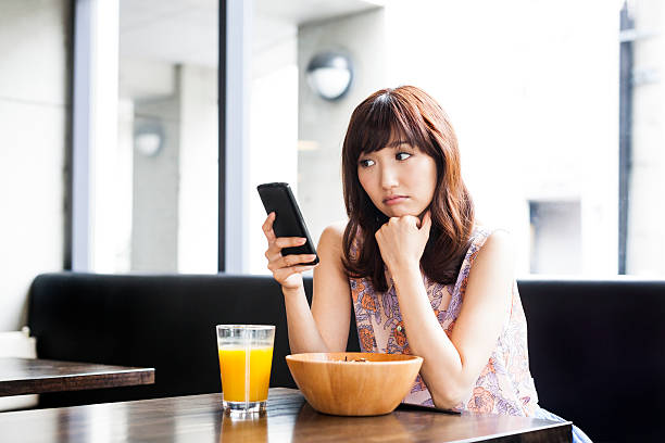 Young girl sadly looking at her phone stock photo