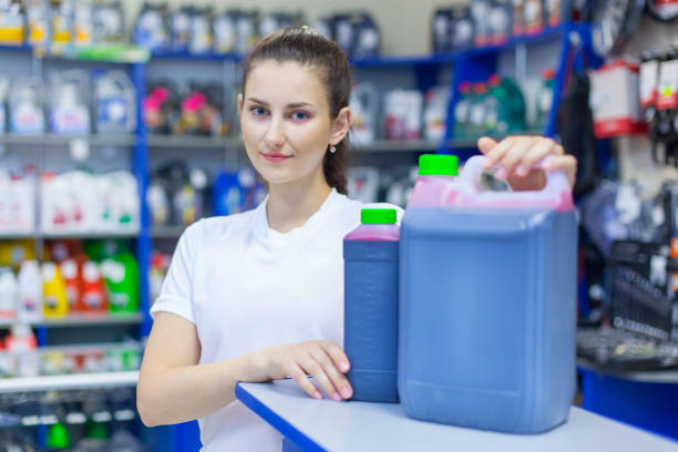 A young girl saleswoman offers a choice of engine oil for the engine in an auto parts store stock photo