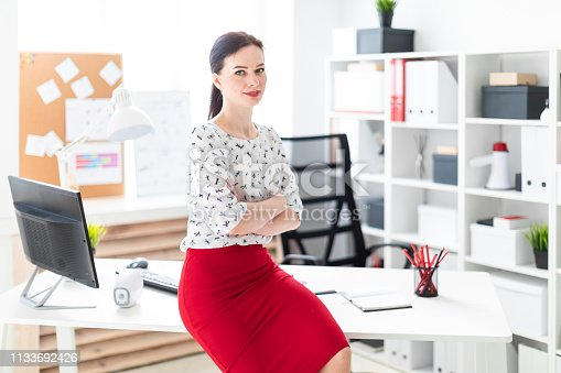 Beautiful young girl working in a bright office. Young girl in blouse and red skirt. Hair girls gathered in the back. photo with depth of field