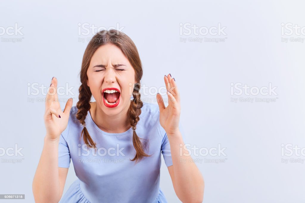 Young girl screams with emotion excited looking at gray background.