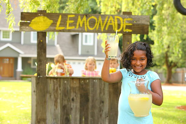 Young girl selling lemonade on a stand Young girl in front of lemonade stand lemonade stand stock pictures, royalty-free photos & images