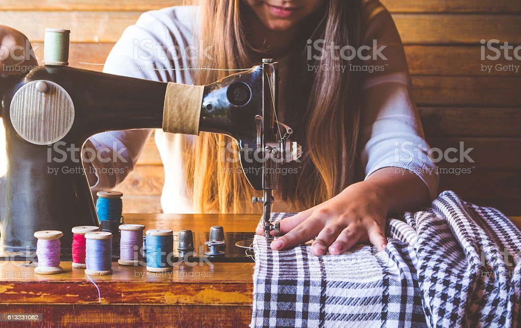 Young girl sews on the old sewing machine stock photo