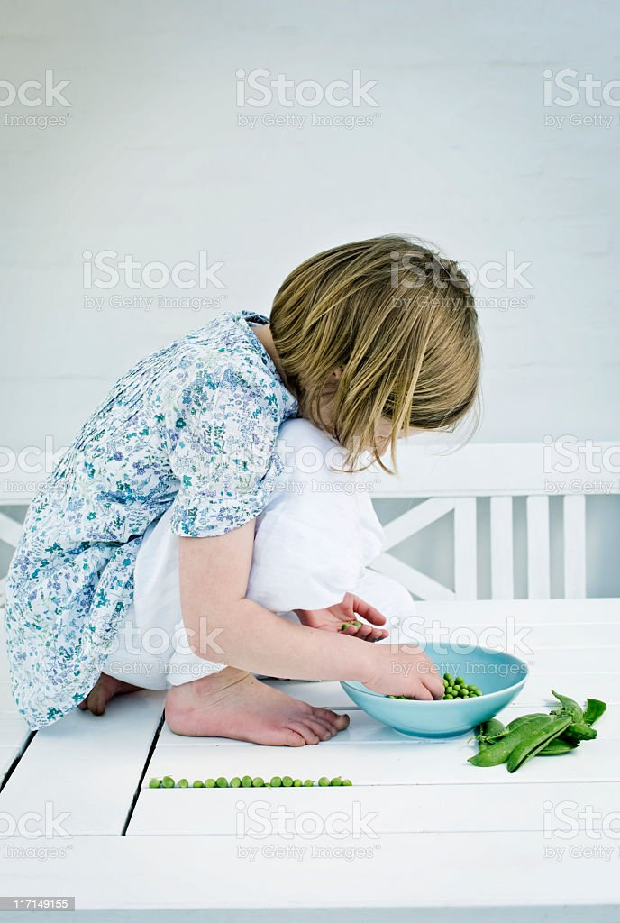 Young Girl Shelling Fresh Peas stock photo