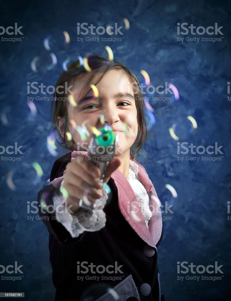 Young girl shooting with bubble gun stock photo