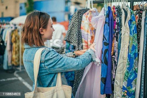 Teenager choosing clothes at a flea market