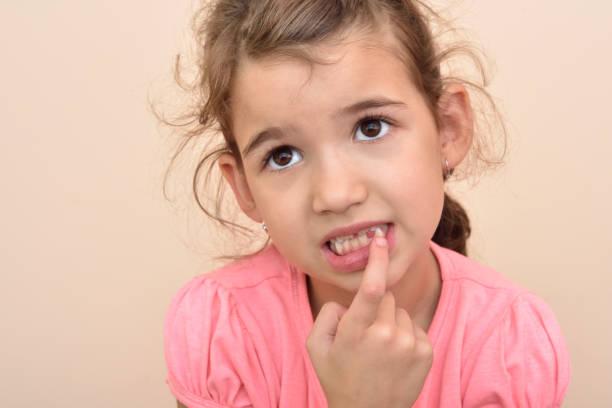 junges mädchen mit einem fehlenden zahn - zahnlücke stock-fotos und bilder