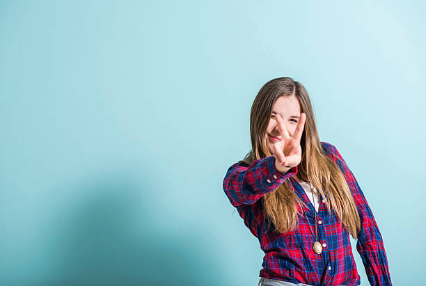 Young girl showing victory sign stock photo