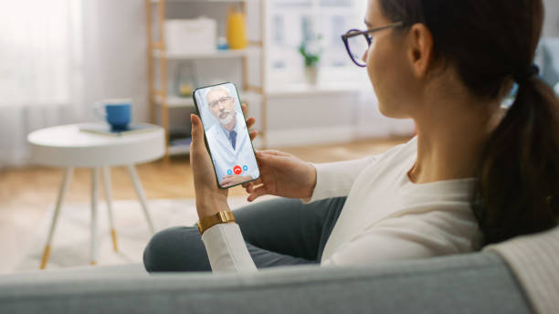Young Girl Sick at Home Using Smartphone to Talk to Her Doctor via Video Conference Medical App. Woman Checks Possible Symptoms with Professional Physician, Using Online Video Chat Application stock photo