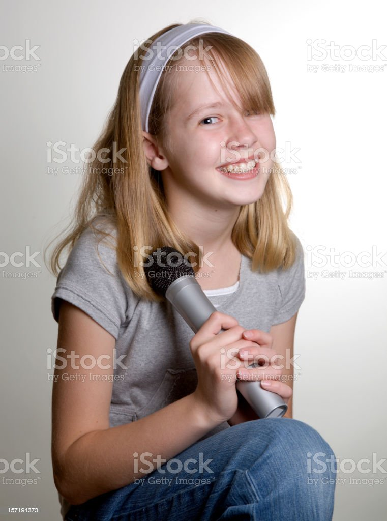 A smiling blonde teenage girl holding a microphone against a white...