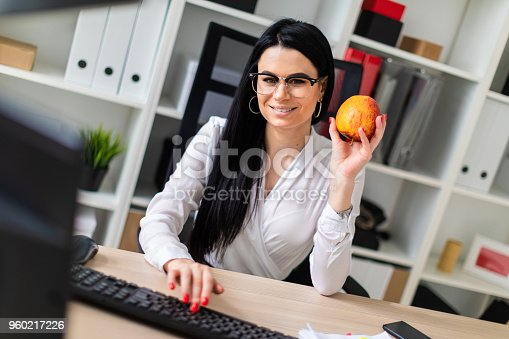istock A young girl sits at a computer desk, holds an apple in her hand and prints on the keyboard. 960217226