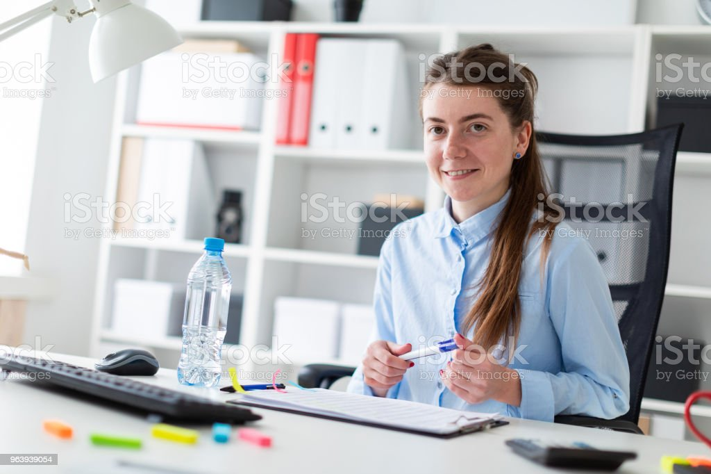 A young girl sits at a table in the office and holds a marker in her hand. - Royalty-free Adult Stock Photo