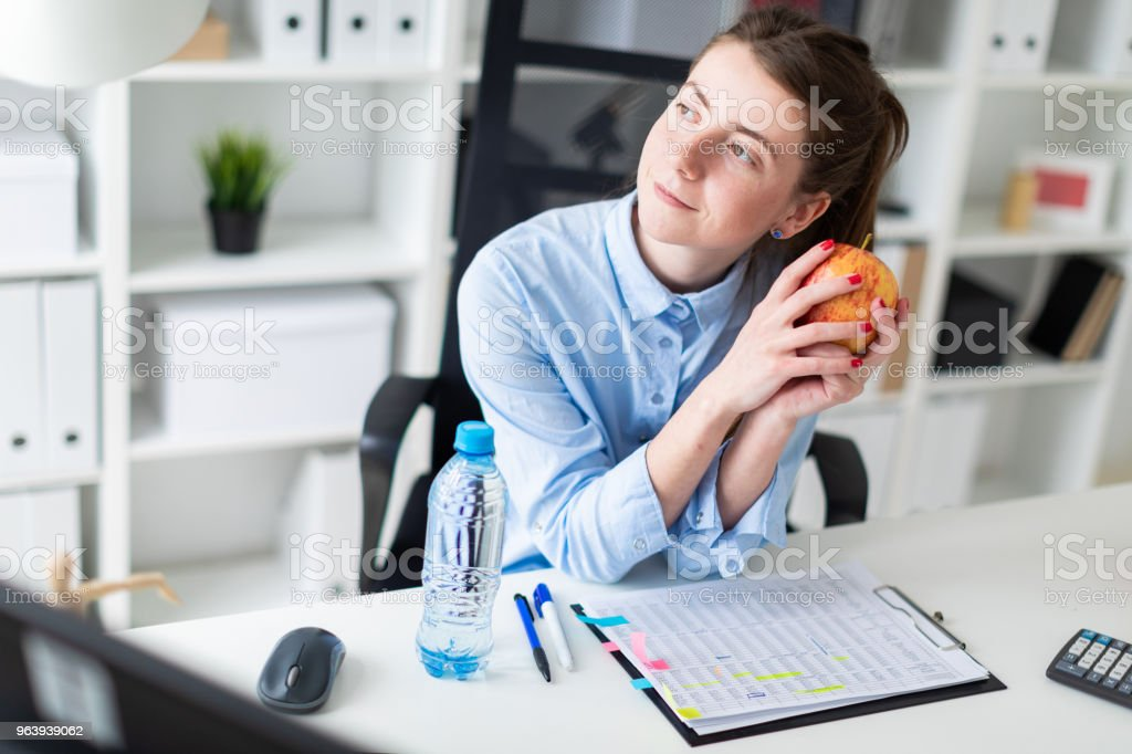 A young girl sits at a table in the office and holds an apple in her hand. - Royalty-free Advice Stock Photo