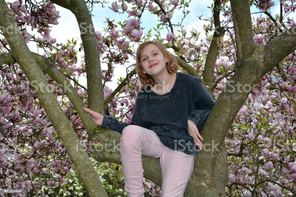Young girl sits in a magnolia tree and smiles forwards foto stock royalty-free