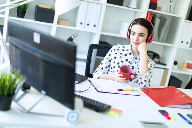 Una joven se sienta en auriculares en una mesa en la oficina, tiene una taza roja en sus manos y mira el monitor. - foto de stock