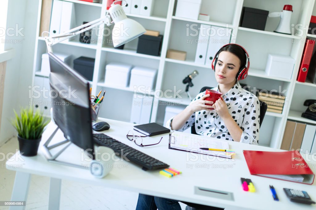 A young girl sits in headphones at a table in the office, holds a red cup in her hands and looks at the monitor. stock photo