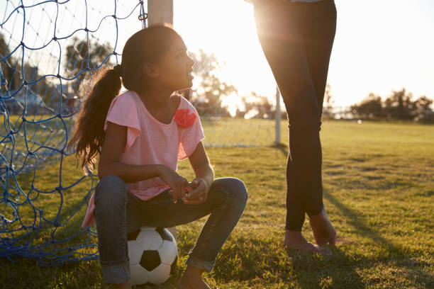 Junges Mädchen sitzt auf Ball neben ihrer Mutter auf dem Fußballplatz – Foto