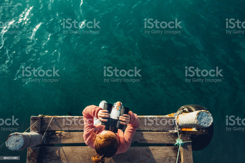 Young Girl Sits On The Pier And Looks At Sea Through Binoculars, Top View. Adventure Vacation Discovery Travel Concept royalty-free stock photo