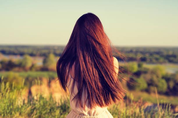 Junges Mädchen sitzt mit dem Rücken zur Kamera und befasst sich mit der Natur – Foto