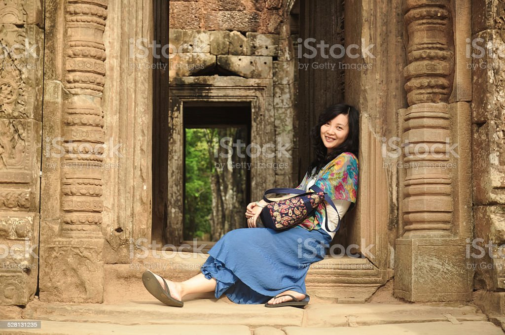 young girl sitting and leaning on ancient doorstep stock photo