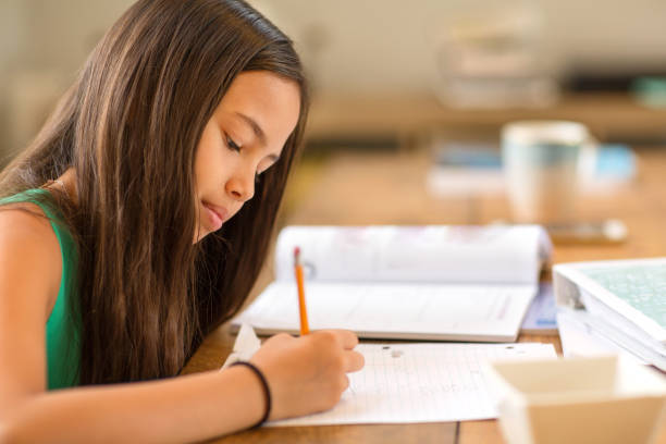 Young Girl Sitting At A Desk And Working On Her Homework stock photo