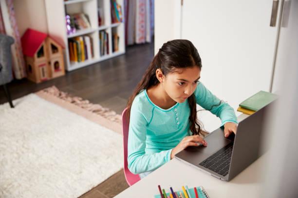 jong meisje zit op bureau in de slaapkamer laptop gebruiken om huiswerk te doen - alleen één meisje stockfoto's en -beelden
