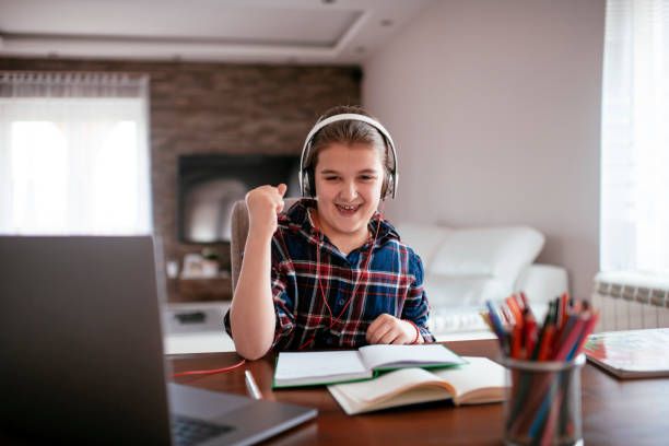 Young Girl Sitting At Desk In living room Using Laptop To Do Homework stock photo stock photo