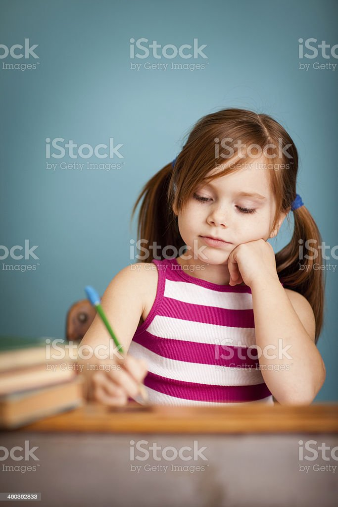 Young Girl Sitting at School Desk Doing Her Schoolwork royalty-free stock photo