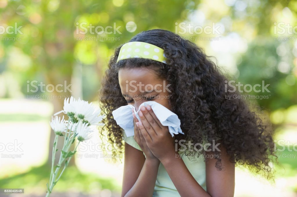 Young girl sitting by flower and blowing her nose in the park stock photo