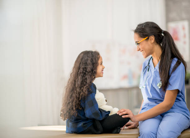 Young Girl Sitting Cross-Legged Face to Face With Nurse stock photo stock photo