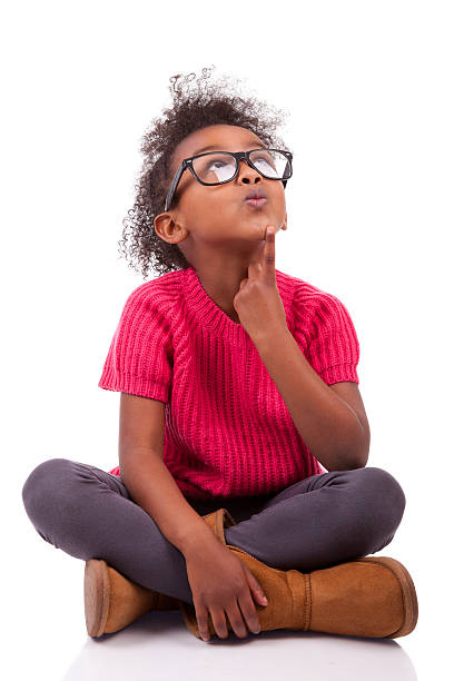 Young girl sitting cross-legged on the floor stock photo