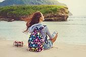若い女の子に座って海の海岸