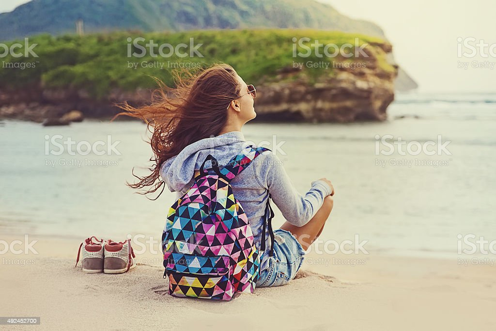 Young girl sitting in a sea shore stock photo