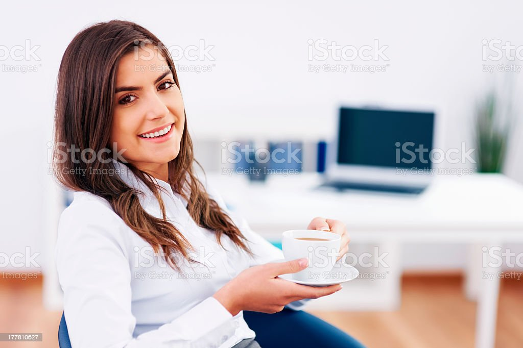 Young girl sitting in an empty office holding a coffee cup royalty-free stock photo