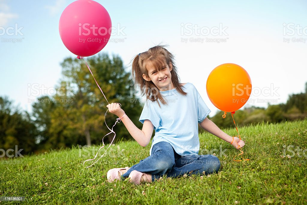 Young Girl Sitting in the Grass and Holding Balloons royalty-free stock photo