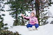 A girl enjoys snowflakes with a dog in a Santa Claus hat.