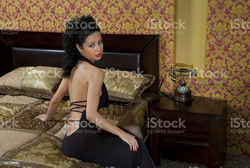 young girl sitting on a bed in a luxurious room, vintage stock photo